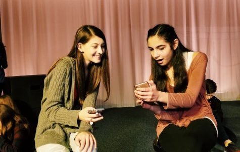 Hannah Moghaddar and Kira Hamburg act surprised as they look at a recent post during rehearsal for the fall play,