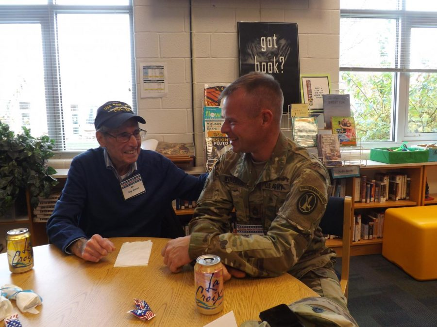 Sigi Almon, Navy force, and Sam Woodhead, Army, speak in the library during a past Veterans Day.