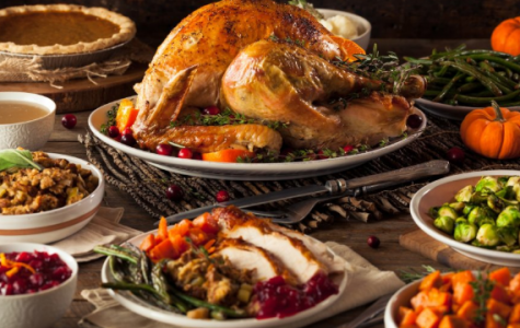 This is an example of a hot traditional and modern Thanksgiving meal. It has a turkey in the middle surrounded by side dishes and desserts but it is modernized by the new cuisine dishes instead of the traditional ones.