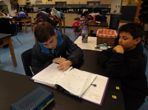 Mason Baldwin, on the left, explains a math problem to Malaki Breenden, on the right, on Dec. 2.