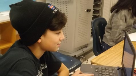 Rehaan works on his articles for the Carson Chronicle with his trademark beanie on his head. Photo by Reema Yaghi.