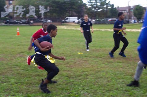 Two students go at it one on one in a flag football battle during after school hours on Rachel Carson's field.
