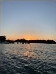 The image shows a sunset over the water.