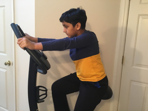 Anay Bansal exercising on his Stationary bicycle, waiting for a safe environment to play outside once COVID-19 ends.